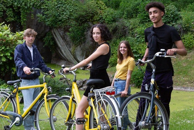 Students on their yellow bikes from De Fietsambassade